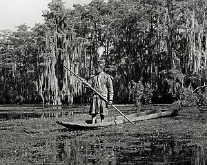 Ebbs photograph of Seminole man in full regalia on dugout canoe, late 1800s early 1900s.