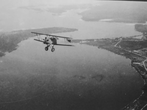 1933 photograph shows Hugh Willoughby flying over Sewall's Point and Willoughby Point in Port Sewall. The insignia of the the New York Yacht Club is on th side of the biplane. (Dale M Hudson via Sandra H. Thurlow's book Sewall's Point.